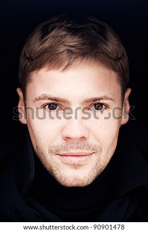 Portrait of young man with brown eyes on a black background - stock photo
