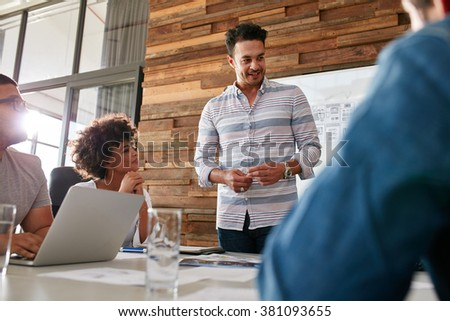Portrait of young man with colleagues having meeting in conference room. Diverse group of young designers brainstorming in boardroom. - stock photo