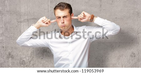 Portrait Of Young Man With Finger In His Ear, Indoor - stock photo