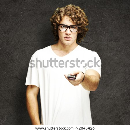 portrait of young man with glasses changing channel with tv control