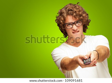Portrait Of Young Man With Glasses Changing Channel With Tv Control On Green Background - stock photo