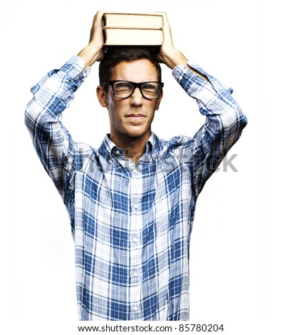 portrait of young man with glasses holding books on his head over white background - stock photo
