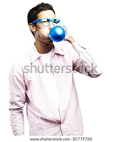 portrait of young man with glasses inflating a blue balloon against a white background - stock photo