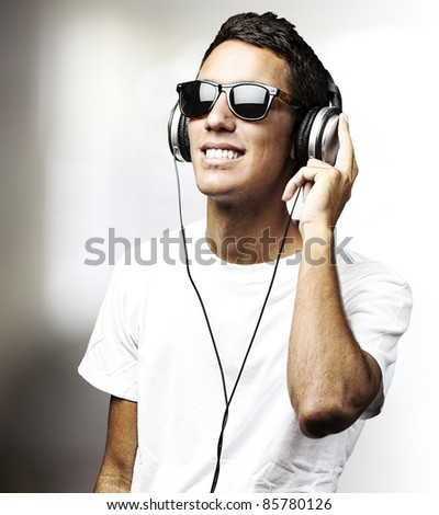 portrait of young man with glasses listen to music in a living room - stock photo