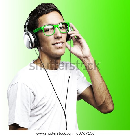 portrait of young man with green glasses listening to music on a green background