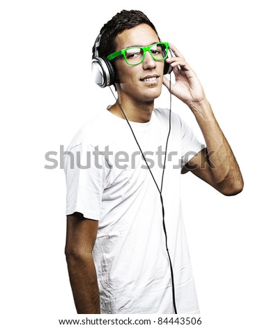 portrait of young man with green glasses listening to music on a white background - stock photo