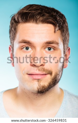 Portrait of young man with half shaved face beard hair. Handsome guy on blue. Skin care and hygiene. - stock photo