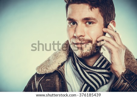 Portrait of young man with half shaved face beard hair talking on mobile phone. Handsome guy on blue. Communication technology. Instagram filter. - stock photo