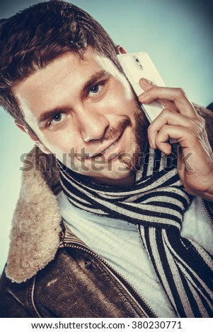 Portrait of young man with half shaved face beard hair talking on mobile phone. Handsome guy on blue. Communication technology.  - stock photo