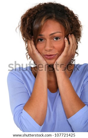 Portrait of young man with hands on face - stock photo