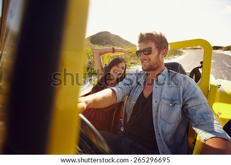 Portrait of young man with his beautiful girlfriend on a road trip. Couple driving in nature in a open car. - stock photo