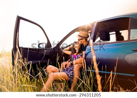 Portrait of young man with his beautiful girlfriend on a road trip.Couple driving in nature in a open car.Young man and young woman on road trip,Loving young couple with sea shore in background. - stock photo