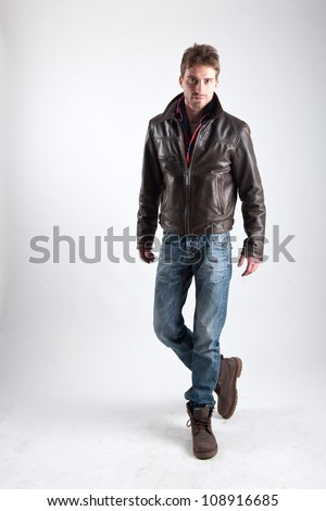 Portrait of young man with leather jacket against white background. - stock photo