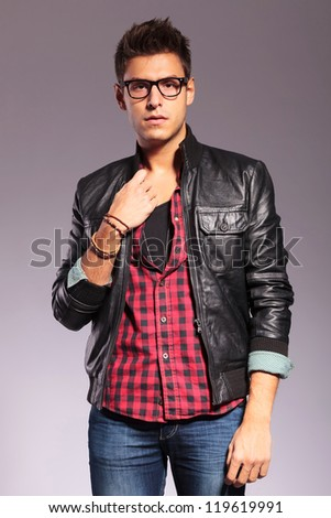 Portrait of young man with leather jacket and glasses against gray background