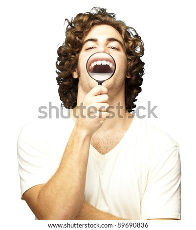 portrait of young man with magnifying glass showing his teeth over white background - stock photo
