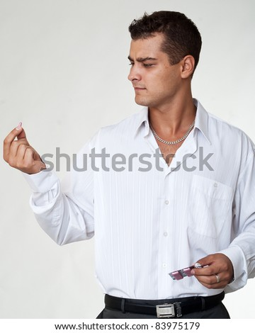 portrait of young man with pills at his hand - stock photo
