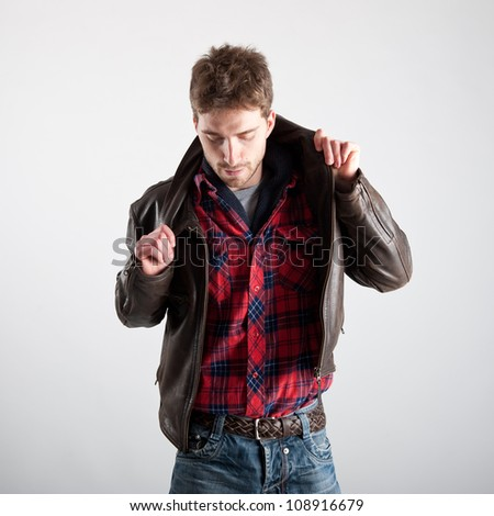 Portrait of young man with plaid shirt and leather jacket.