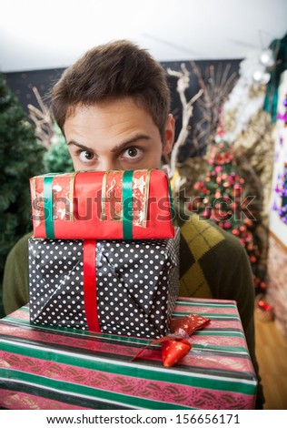 Portrait of young man with raised eyebrows looking over stacked Christmas gifts in store - stock photo