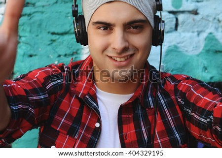 Portrait of young man with red headphones on the street. - stock photo