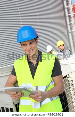 Portrait of young man with security helmet on - stock photo