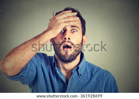Portrait of young man with shocked facial expression - stock photo