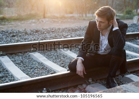 Portrait of young man with suit sitting in rail way - stock photo