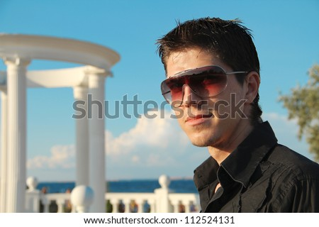 portrait of young man with sunglasses laughing over blue sky outdoors
