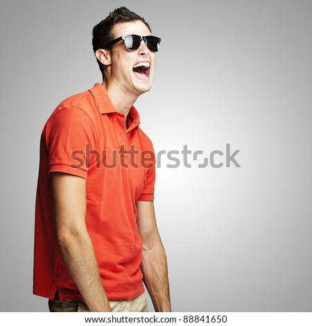 portrait of young man with sunglasses laughing over grey background - stock photo