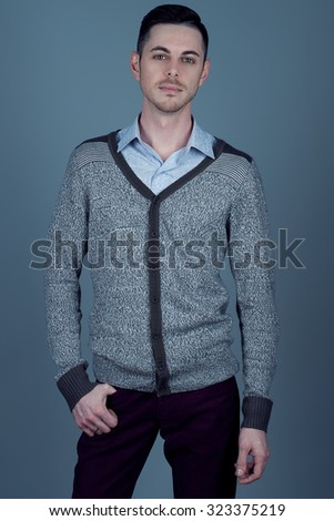 Portrait of young man with very handsome face in grey jumper and in blue shirt with stylish haircut posing over grey background. Perfect skin & hair. Studio shot