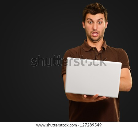 Portrait Of Young Man Working On Laptop On Black Background
