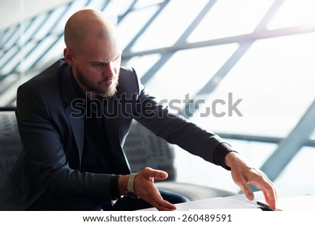 Portrait of young managing business man organizing papers and documents sitting in big light office, soft focus, filtered image with flare light from the window - stock photo
