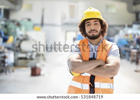 Portrait of young manual worker standing arms crossed in metal industry