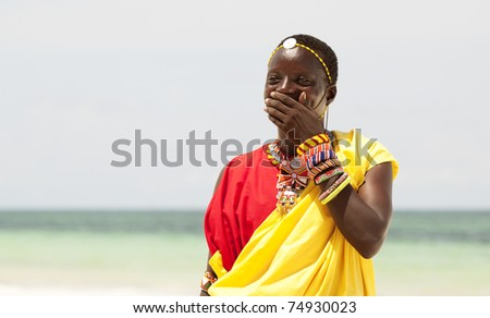 Portrait of young Masai man posing on bright sunny ocean beach; portrait with narrow focus - stock photo