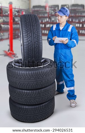 Portrait of young mechanic wearing blue uniform and using a digital tablet to check tires at workshop - stock photo