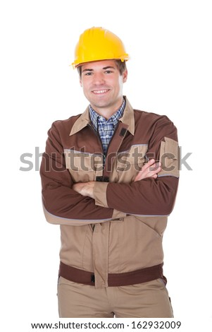 Portrait Of Young Mechanic Wearing Hardhat With Arm Crossed - stock photo