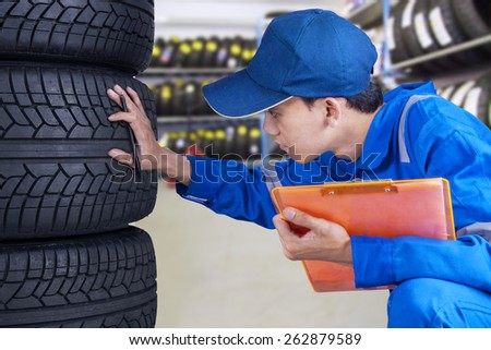 Portrait of young mechanic with a blue uniform checking a stack of tires while holding a clipboard - stock photo