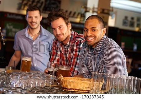 Portrait of young men drinking beer in pub, sitting at counter, smiling. - stock photo