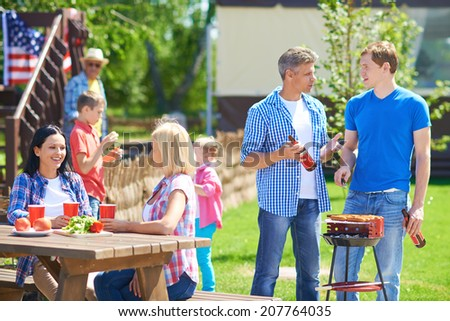 Portrait of young men frying sausages and talking in the countryside at weekend with their families near by - stock photo