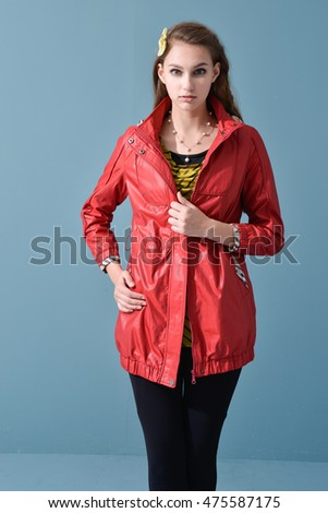 portrait of young model in red jacket dress posing on blue background