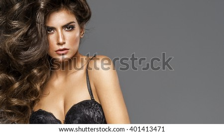 Portrait of young model wear bra in fashionable curly hair