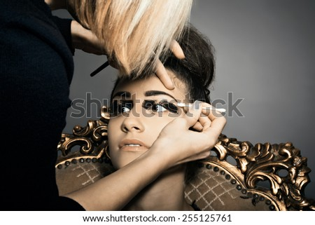 Portrait of young model with make-up artist at work - stock photo