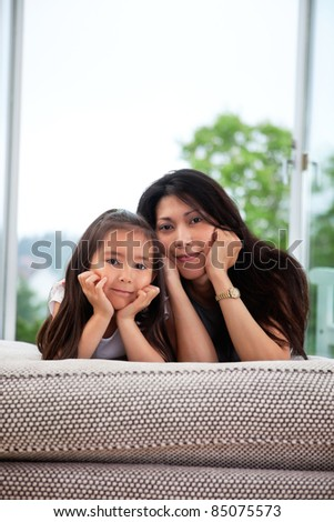 Portrait of young mother and cute daughter lying on a couch - stock photo