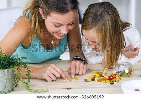 Portrait of young mother and daughter playing with sweets at home.