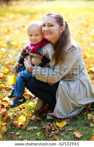 Portrait of young mother and her little daughter outdoors on sunny autumn day - stock photo