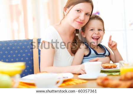 Portrait of young mother and her son having breakfast together - stock photo
