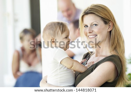 Portrait of young mother carrying baby on porch with family behind - stock photo