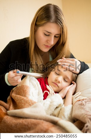 Portrait of young mother embracing sick daughter and checking thermometer - stock photo
