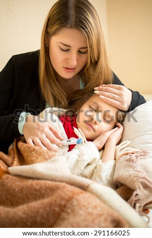 Portrait of young mother hugging sick girl in bed - stock photo