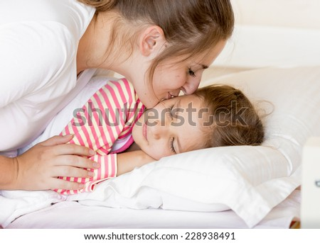 Portrait of young mother kissing sleeping daughter at morning - stock photo