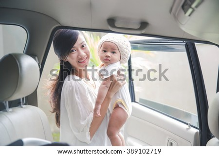 portrait of young mother ready to put her baby in a car seat